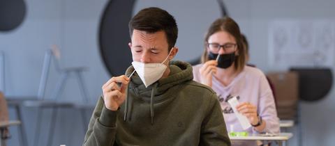 Ein Schüler und eine Schülerin führen sich Corona-Selbsttest-Stäbchen in die Nase. Die Schutzmaske ist hierfür herunter gezogen. Sie sitzen einzeln an Tischen in einem Klassenzimmer.