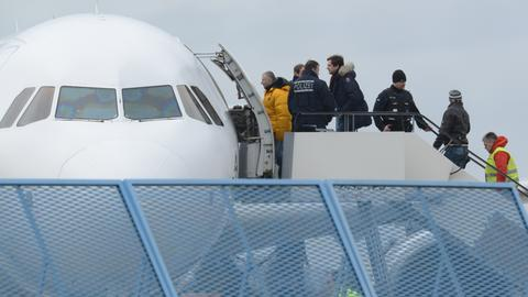 Bundespolizisten führen abzuschiebende Flüchtlinge in ein Flugzeug