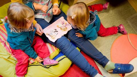 Eine Erzieherin liest zwei Mädchen in der Kita aus einem Buch vor.