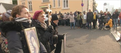 Abtreibungsgegner beten, im Hintergrund Gegendemonstranten