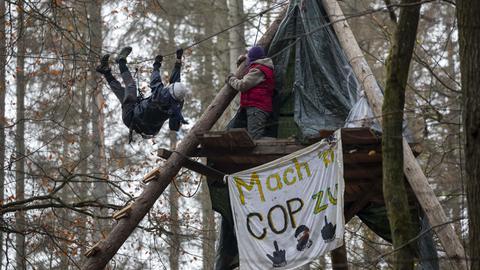 Ein Aktivist hangelt sich an einem Seil in luftiger Höhe entlang.