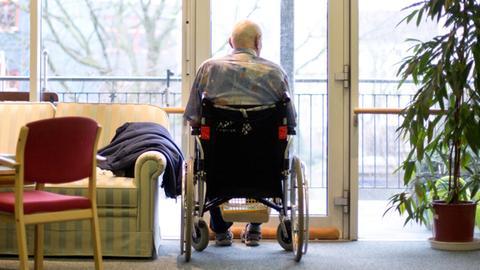 Ein Mann sitzt in einem Rollstuhl und schaut aus einer Balkontür hinaus ins Freie.