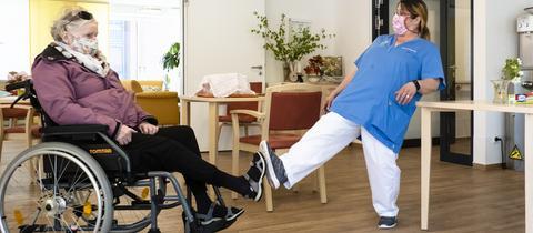 Eine Rollstuhlfahrerin und eine pflegerin begrüßen sich mit einer Fußberührung.