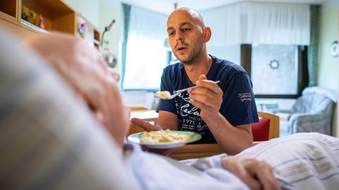 Altenpfleger reicht Essen an