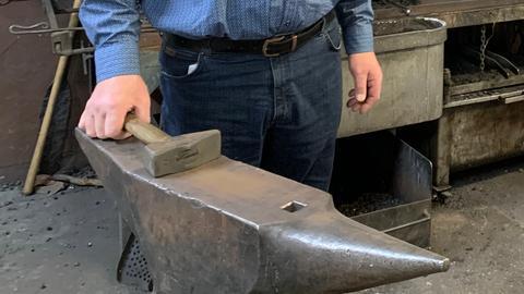 Ein Hammer liegt auf einem Amboss
