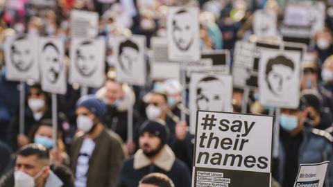 Menschen halten ein Plakat hoch.