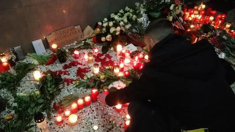 Ein improvisierte Gedenkstätte im Eingangsbereich eines Wohnhochhauses in Hanau-Kesselstadt. Ein Mann beugt sich über unzählige auf dem Boden abgelegte Blumen und Grablichter.
