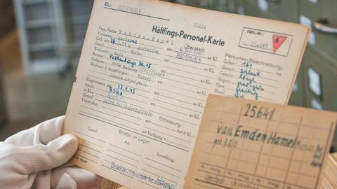 Hand mit Handschuhen, die historische Dokumente über KZ-Häftling in der Hand hält