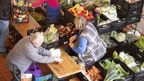 Eine Rentnerin versorgt sich bei einer Tafel in der Kirche St. Lioba mit Nahrungsmitteln