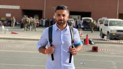 Ein Mann mit Rucksack steht an einer Straße, im Hintergrund ein Flughafengebäude und Soldaten in Tarnkleidung.