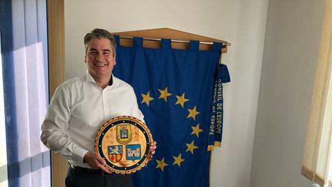Aßlars Bürgermeister Schwarz mit einem Teller, der die Wappen der Partnerstädte zeigt.