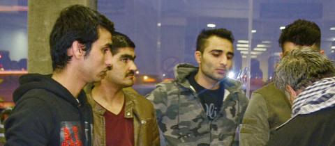 Eine Gruppe Männer steht nachts vor einer Glasscheibe.