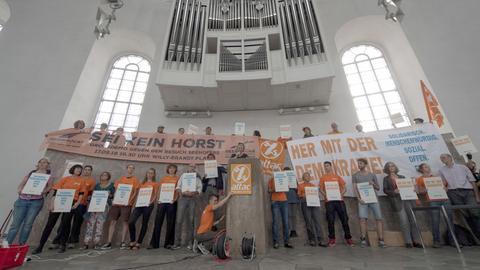 Ein gutes Dutzend Aktivisten von Attac posieren vor der Empore im Innenraum der Paulskirche.