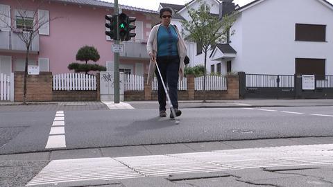 Lydia Zoubek beim Überqueren einer Straße an einer Ampel.