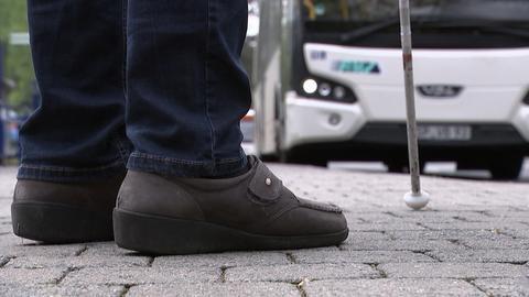 Lydia Zoubek steht an einer Bushaltestelle. Man sieht ihre Schuhe in Großaufnahme und einen Teil ihres Blindenstocks, im Hintergrund fährt ein Bus heran.