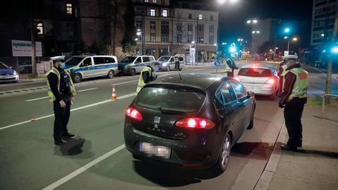 Polizisten kontrollieren Autos und deren Insassen.