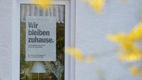 """Ein Schild am Fenster mit der Aufschrift """"Wir bleiben zuhause"""""""