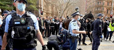 Ein Demonstrant wird von der Polizei bei Anti-Lockdown-Protesten in Australien festgenommen.