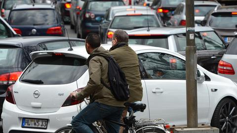 Zwei Radfahrer stehen in Frankfurt in einem Stau von Autos