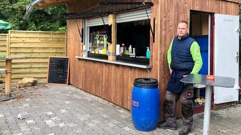 Mann steht neben einer Imbissbude