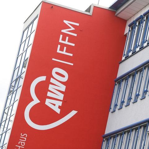 """Das Bürogebäude des AWO Kreisverbandes in Frankfurt. An der roten Hauswand steht in großen Lettern """"AWO FFM""""."""
