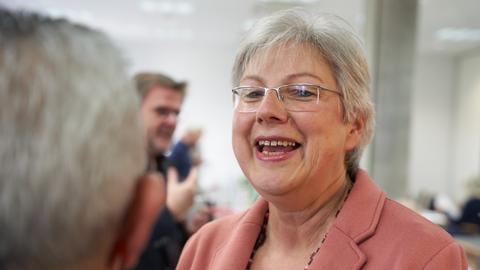 Petra Rossbrey lacht einen Mann an, vom dem im Vordergrund nur der Hinterkopf zu erkennen ist.