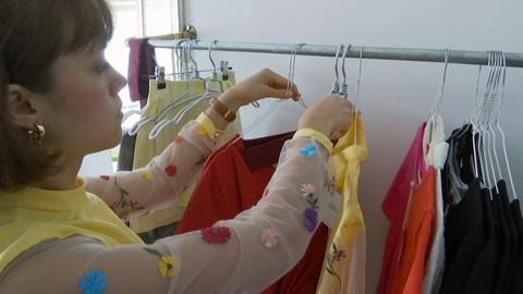 Designerin Ricarda Haase sortiert Kleidung an einer Kleiderstange.