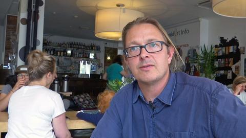 Hostelbesitzer Peter Weißbach sitzt im Frühstücksraum.