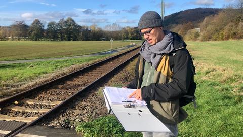 Mann steht mit Ordner voller Papier vor Bahngleisen