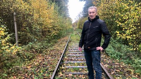Mann steht auf Gleisen