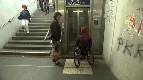 Rollstuhlfahrerin vor defektem Aufzug