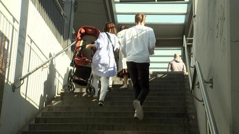 Mutter trägt Kinderwagen eine Treppe hoch