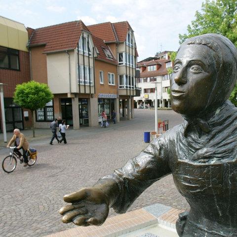 Märchenerzählerin Dorothea Viehmann blickt von einem Brunnen auf Baunatals Innenstadt