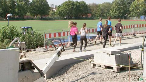 """Eine Baustelle neben einem Schulsportplatz. Im Vordergrund liegt Baumaterial. Im Hintergrund joggen einige Schülerinnen und Schüler """"aus dem Bild""""."""
