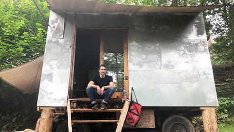 Ein junger Mann sitzt auf hözernen Stufen an der Tür zu seinem Bauwagen. Die Behausung ist mit Blech eingekleidet und hat große Markisen.
