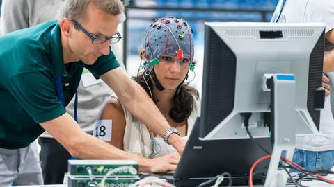 Frau trägt elektrodenbesetzte Kappe und sitzt vor PC-Bildschirm