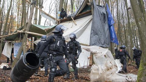 Die Polizei beseitigt Behausungen von Waldbesetzern.