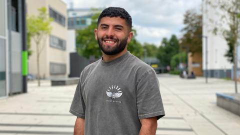 Yazan steht lächelnd in einer Straße
