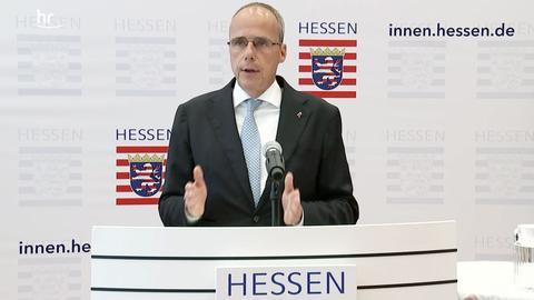 Beuth während der Pressekonferenz, im Hintergrund das hessische Wappen.