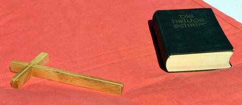 Kreuz und Bibel liegen auf einem roten Tuch