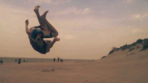 Max Sprenger macht einen Salto am Strand