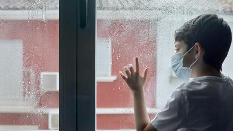 Ein Junge steht am Fenster und schaut raus. Er trägt eine OP-Maske. Draußen regnet es.