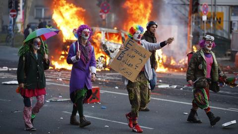 Demonstranten ziehen durch Frankfurt, im Hintergrund brennt ein Auto