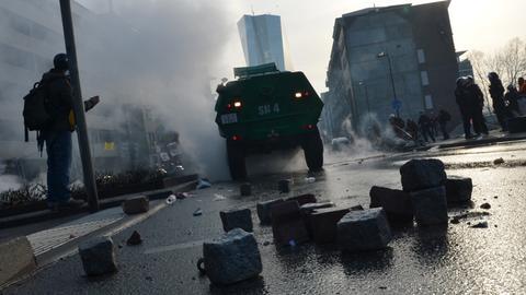 Pflastersteine liegen nach Krawallen auf der Straße, im Hintergrund das neue EZB-Gebäude