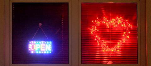 """Ein """"Open""""-Schild hängt neben einem roten Herz in einem Fenster."""