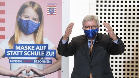 Hessens Ministerpräsident Bouffier vor einem der Plakate der neuen Kampagne des Landes in der Corona-Pandemie