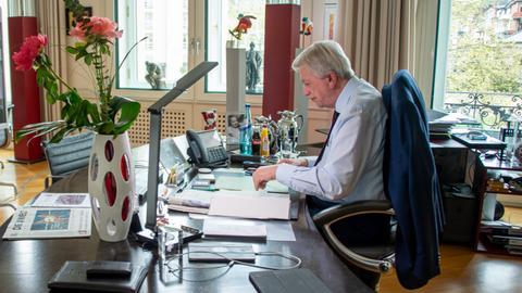 Bouffier am Schreibtisch, auf einem Bildschirm sind die Vertreter in einer Online-Konferenz zu sehen.