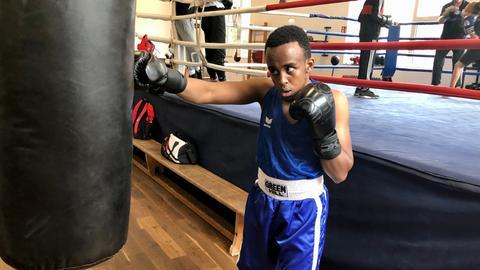 Junger Mann mit Boxhandschuhen trainiert