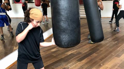 Junge boxt auf Boxsack ein