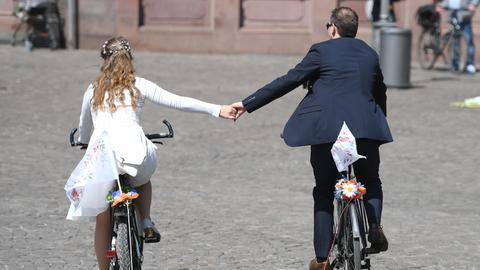 Ein Brautpaar fährt nach der Trauung im Frankfurter Römer auf Fahrrädern über den Römerberg.